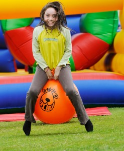 Brownie on spacehopper in front of bouncy castle