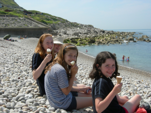 Three guides sitting on pebble beach in sunshine eating icecreams
